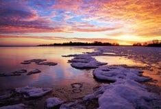 与湖和日落火热的天空的冬天风景。 免版税库存照片
