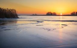 与湖和日落火热的天空的冬天风景 免版税库存图片