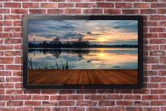 与湖墙纸在日落-砖墙的聪明的电视在背景中 图库摄影