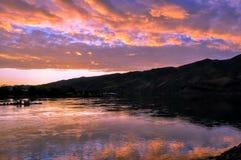 与湖的剧烈的日落风景,天空反射、渔船和山麓小丘爱达荷和华盛顿边界的斯内克河  免版税库存照片