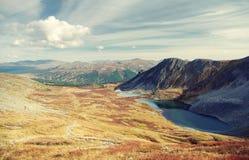 与湖的山高地黄色谷背景的  库存照片