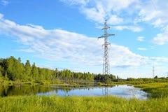 与湖的风景和一条输电线的支持晚上 免版税库存图片