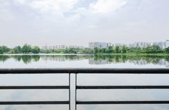 与湖边城市的钢扶手栏杆在背景中在多云夏天 免版税库存图片