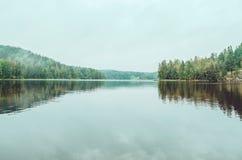 与湖,杉树,自然石海岸的美好的秋天风景在卡累利阿共和国,拉多加,北 免版税库存照片