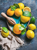 与湿叶子的新近地被采摘的柠檬在蓝色陶瓷板材 免版税库存图片