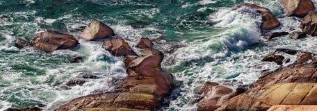 与湿岩石的美丽的风雨如磐的海滨 库存照片