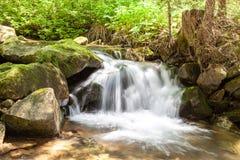 与湿岩石的落下的瀑布特写镜头非常光滑的水 库存照片