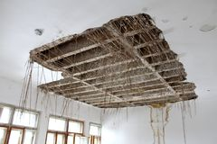 与湿气毁坏的垂悬的绝缘材料的粉碎的天花板 免版税库存照片