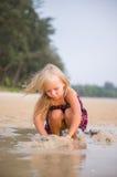 与湿沙子的可爱的女孩戏剧在日落海洋海滩 库存图片