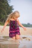 与湿沙子的可爱的女孩戏剧在日落海洋海滩 图库摄影