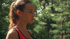 与湿面孔的年轻热的体育女孩立场在森林和下落流动在面颊下 股票视频
