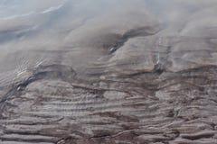 与湿黑泥沙沙子泥的冰河河岸岸 免版税库存图片