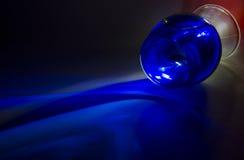 与溢出的蓝色液体的玻璃 图库摄影