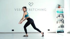 与滑动的圆盘的年轻女人蹲坐在慢动作的白光健身房锻炼 影视素材