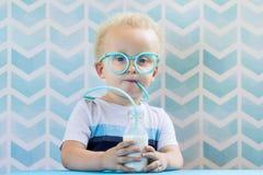 与滑稽的玻璃秸杆的逗人喜爱的小男孩饮用奶 免版税库存照片