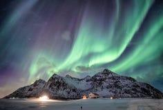 与满天星斗的结束雪山脉的极光borealis与照明房子在弗拉克斯塔,罗弗敦群岛海岛,挪威 免版税库存图片