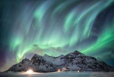 与满天星斗的结束雪山脉的极光borealis与照明房子在弗拉克斯塔,罗弗敦群岛海岛,挪威 图库摄影