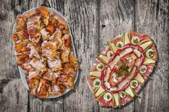 与满盘的传统被装饰的开胃菜盘唾液在老破裂的片状木庭院表上的烤猪肉 免版税库存图片