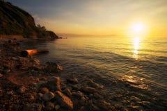 与漂流木头、海和日落天空的美好的风景 免版税库存图片