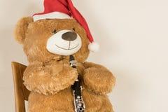 与演奏单簧管的圣诞节盖帽的被充塞的熊 库存图片