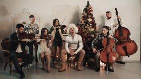 与演奏歌曲的歌手的串五部合唱在有圣诞节装饰的屋子里 股票视频