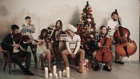 与演奏歌曲的歌手的串五部合唱在有圣诞节风景的屋子里 股票视频