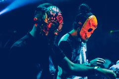 与演奏混合的音乐的面具的令人惊讶的Djs在夏天集会节日 免版税库存照片
