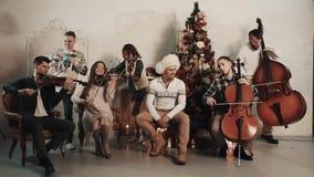 与演奏音乐的歌唱者的串五部合唱在有圣诞节装饰的屋子里 股票录像