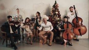 与演奏音乐的歌手的串五部合唱在有圣诞节装饰的屋子里 影视素材