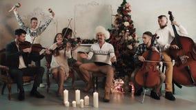 与演奏音乐的歌手的串五部合唱在有圣诞节装饰的屋子里 股票视频