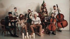 与演奏音乐的歌手的串五部合唱在有圣诞节风景的屋子里 股票录像