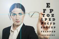 与激光全息图的妇女玻璃和测试在黑暗的视觉桌 免版税图库摄影