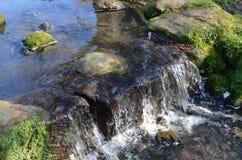 与瀑布的小河 免版税库存图片