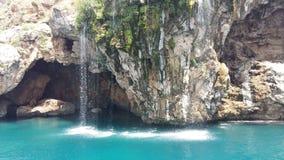 与瀑布的岩石在海 库存照片