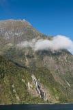 与瀑布的峭壁在Milford Sound,新西兰 库存图片