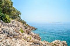 与灌木的多岩石的海滩和树和透明的蓝色Adriati 图库摄影