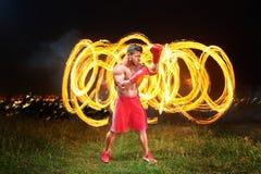 与火和火焰的强的肌肉男性战斗机在他的bac后 免版税图库摄影