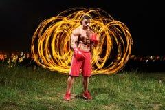 与火和火焰的强的肌肉男性战斗机在他的bac后 免版税库存照片