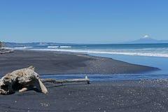 与火山和黑沙子的海滩风景 免版税库存照片