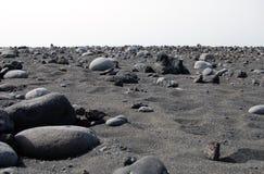 与火山的石头的黑沙子海滩 库存图片