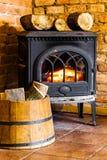 与火火焰和木柴的壁炉在桶内部。加热。 免版税图库摄影