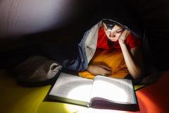 读与火炬的男孩一本书在晚上 免版税库存照片