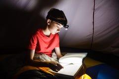 读与火炬的男孩一本书在晚上 免版税库存图片