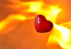 与火焰的灼烧的心脏反对火背景 免版税图库摄影