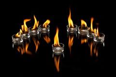 与火焰的玻璃杯子 库存照片
