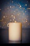 与火焰的蜡烛在蓝色bokeh背景的木桌上 库存图片