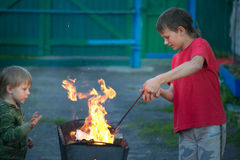 与火的儿童游戏在格栅 免版税库存图片