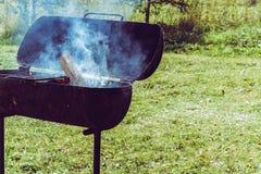 与火的金属在晴朗的夏天背景的火盆和烟 木炭的准备从木头的在生锈的一串shish烤肉的 免版税库存照片