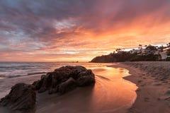 与火红色天空的新月形海湾日落 免版税库存图片