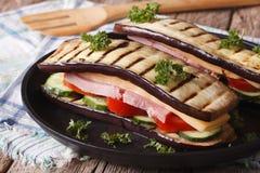 与火腿和乳酪特写镜头的鲜美茄子三明治在板材 库存图片